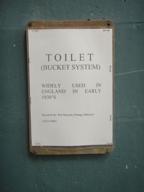 "Sign on wall reading: ""Toilet (Bucket system). Widely used in England in the 1930s."""
