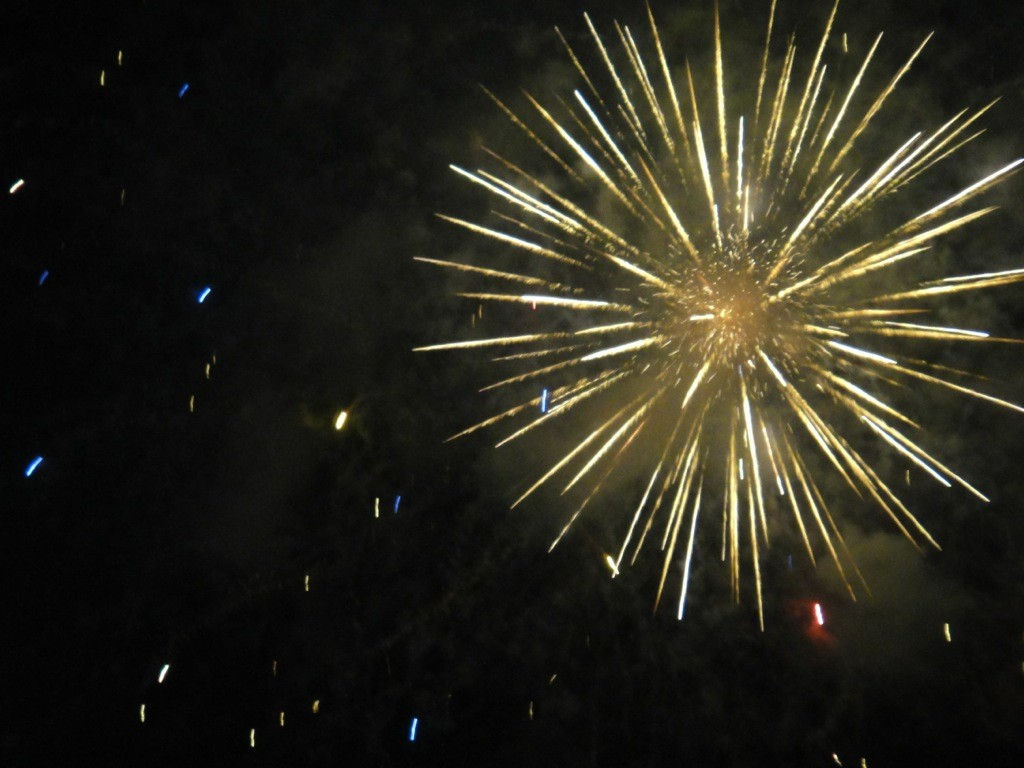 Bright white explosion as a firework goes off in the night sky.