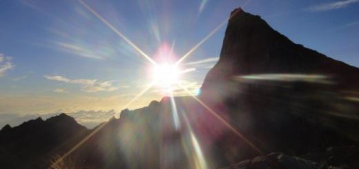 sun bursts above peaks on the summit of mount kinabalu, borneo, malaysia