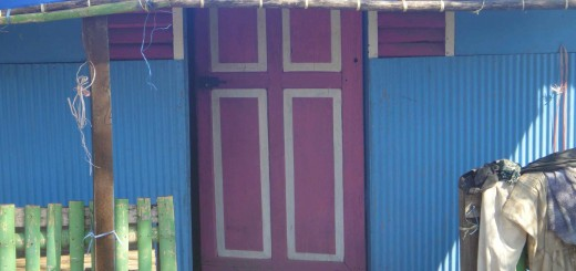 blue and pink shack, with green fence and washing lined up outside. Makassar harbour, indonesia.
