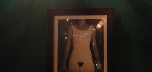 Framed picture on wall of girl in white glass holding martini glass at crotch level.