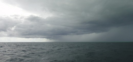 Storm clouds gather over a flat dark sea. Off Pulau Derawan, Indonesia.