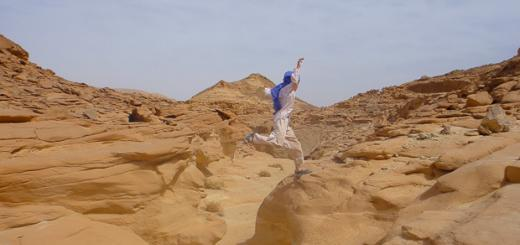 Family travel in Sinai, Egypt: child leaping over a wadi.