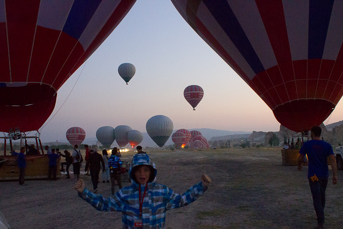An excited Zac framed by two balloons, outside Goreme, Cappadocia.