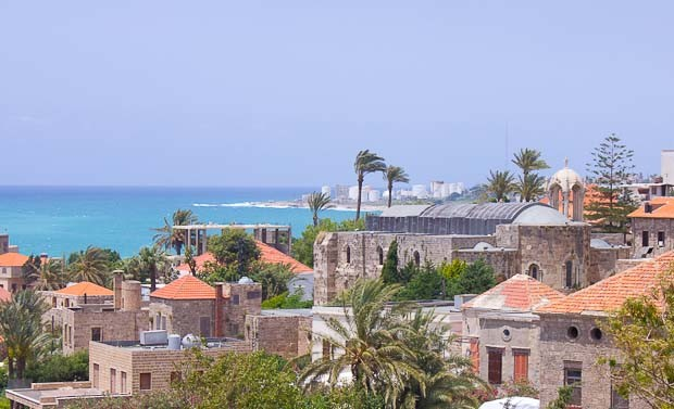 View over Byblos old town with red roofed houses, sea and palms.