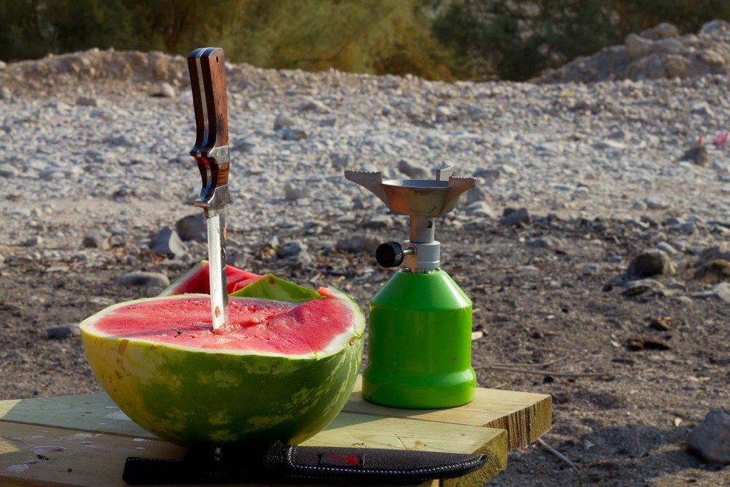 Watermelon, hunting knife and camping stove.