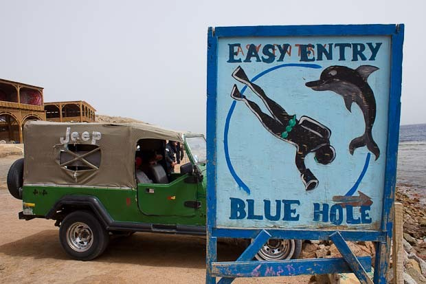 "Sign for ""easy entry"" to the Blue Hole, with jeep, in Dahab, Sinai."
