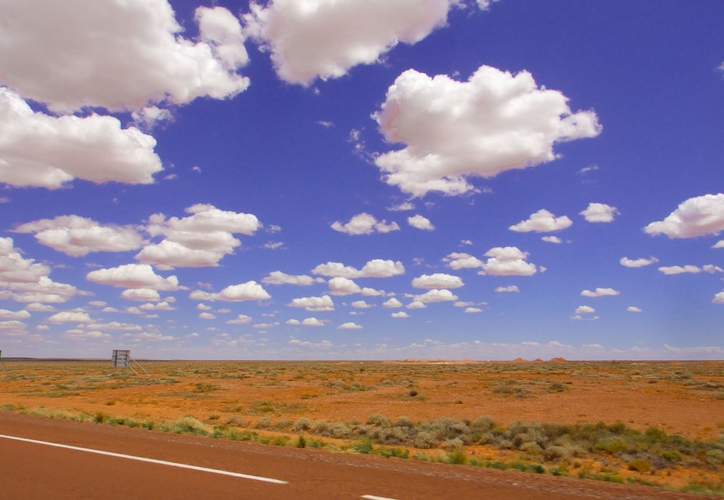 clouds, road and red earth in outback australia.