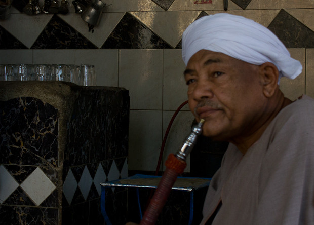 Older man enjoying a sheesha and watching a movie in an ahwa in Daraw, Egypt.