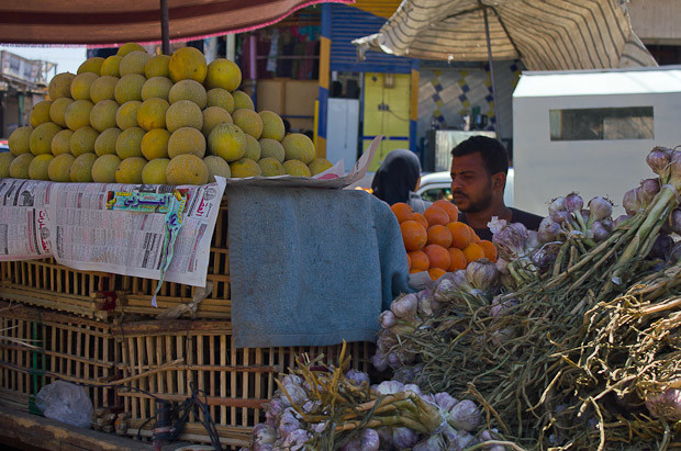 Tired stallholder behind his fruit stand in a small Egyptian town, Daraw.