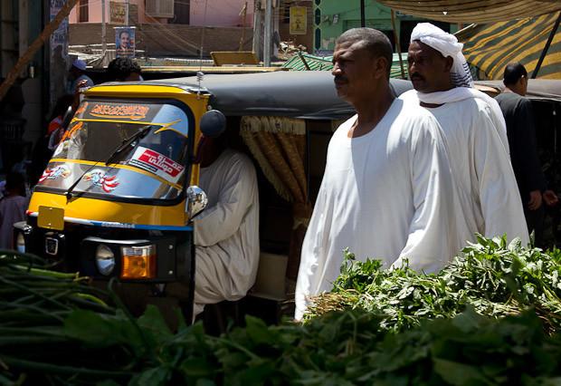 Men in Arab robes walk between stalls and a tuk-tuk.