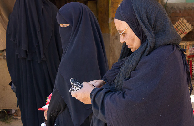 Middle-aged lady in headscarf, shawl and abaya checking her texts.