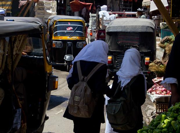 School girls make their way through a mass of tuk-tuks on market day in Daraw.