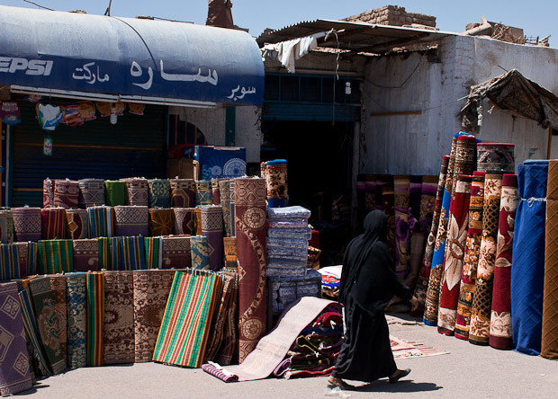 A lady in black walks past a carpet shop on market day in Daraw.