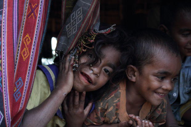 Nome, Timor: giggling, snotty kids peer out from behind woven cloths.