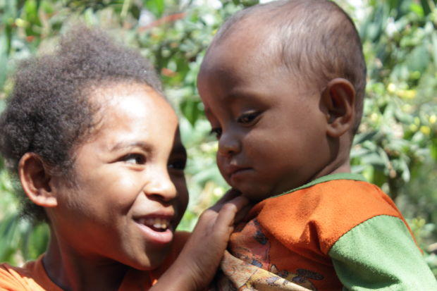 Nome, Timor: a little girl holds her baby brother. He is terrified of us, and about to cry. She finds it funny.