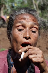Nome Timor -- woman exhales after smoking a cigarette.