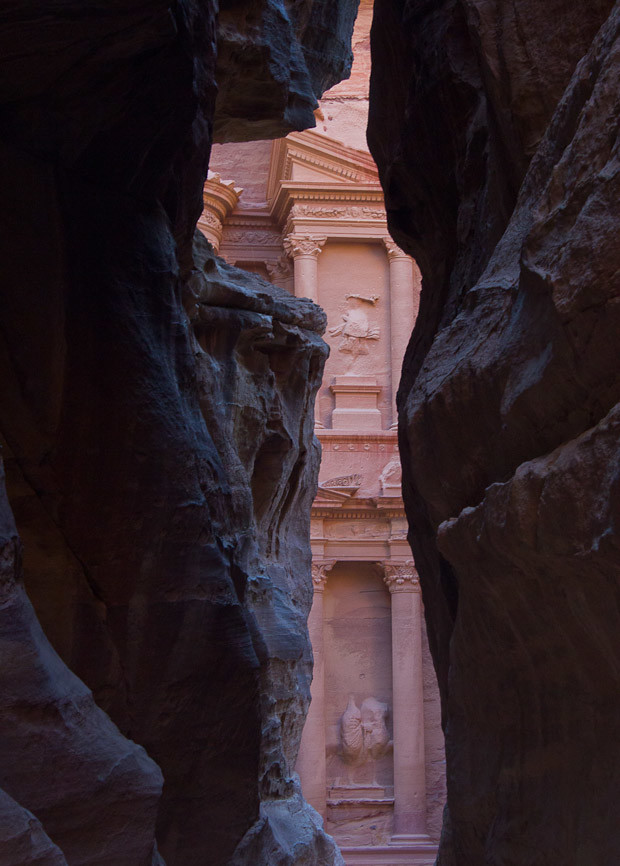 The Treasury at Petra emerges from the darkness of the Siq.