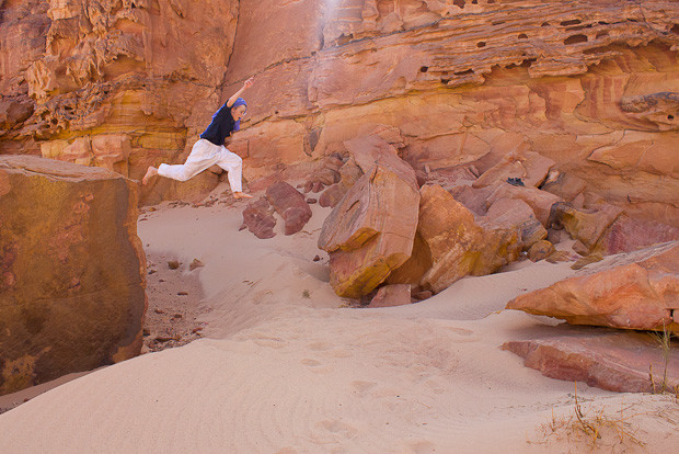 Family travel Egypt: child jumping from red rock onto soft sand.