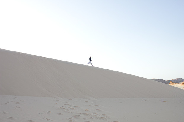 FAmily travel Egypt: child running down sand dune in the Sinai Desert.