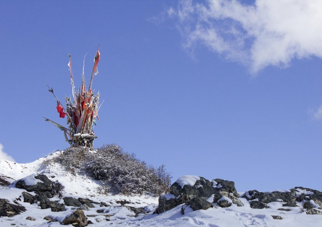 Horse trekking Songpan: flags in snow in the mountains