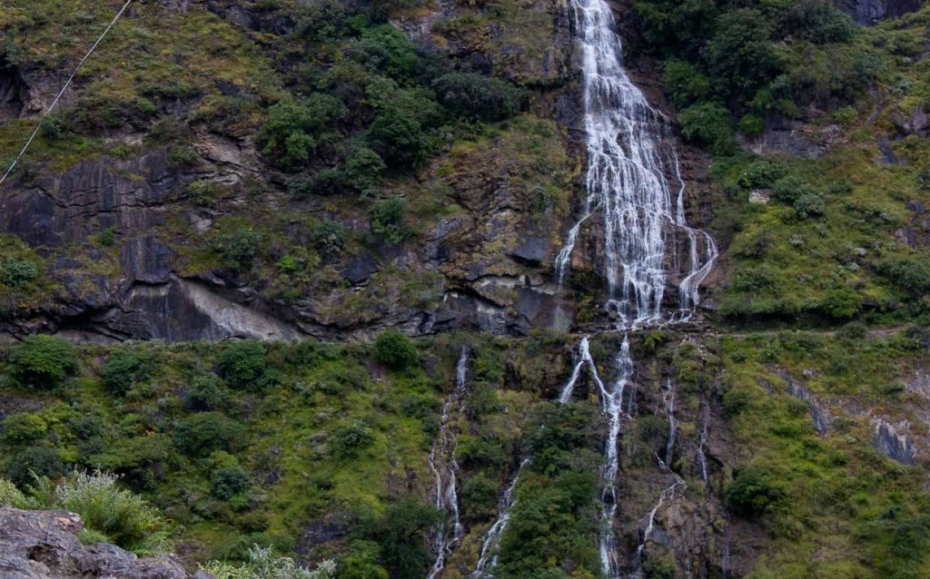 Waterfall running across narrow, cliffside path in Tiger Leaping Gorge, China.