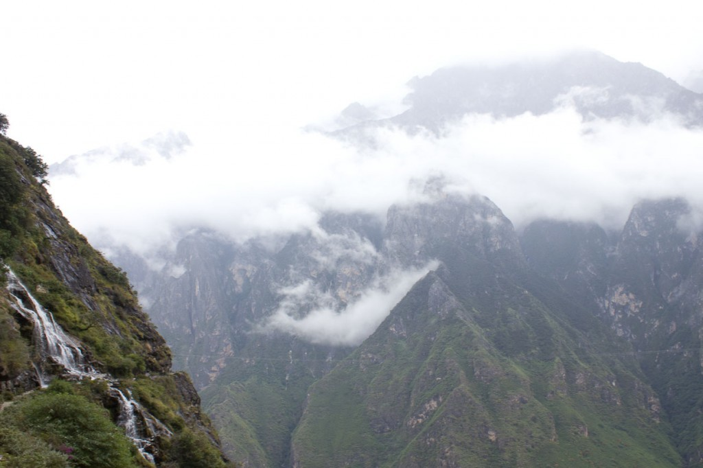 View of waterfall dropping away with mountains in the background, Tiger Leaping Gorge, Yunnan, China.