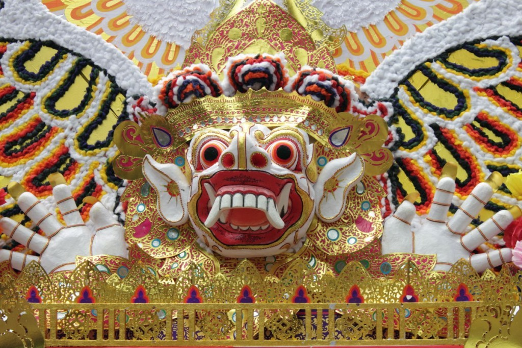 Bali Funeral: the gilded face of protective demon, known as a bhoma, on a funeral tower in Ubud, Bali.