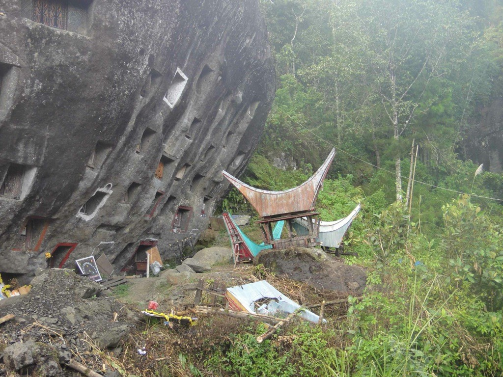 Broken graves in the shape of tongkonan houses below cave grave outcrop. Lokomata, Tana Toraja, Sulawesi, Indonesia.