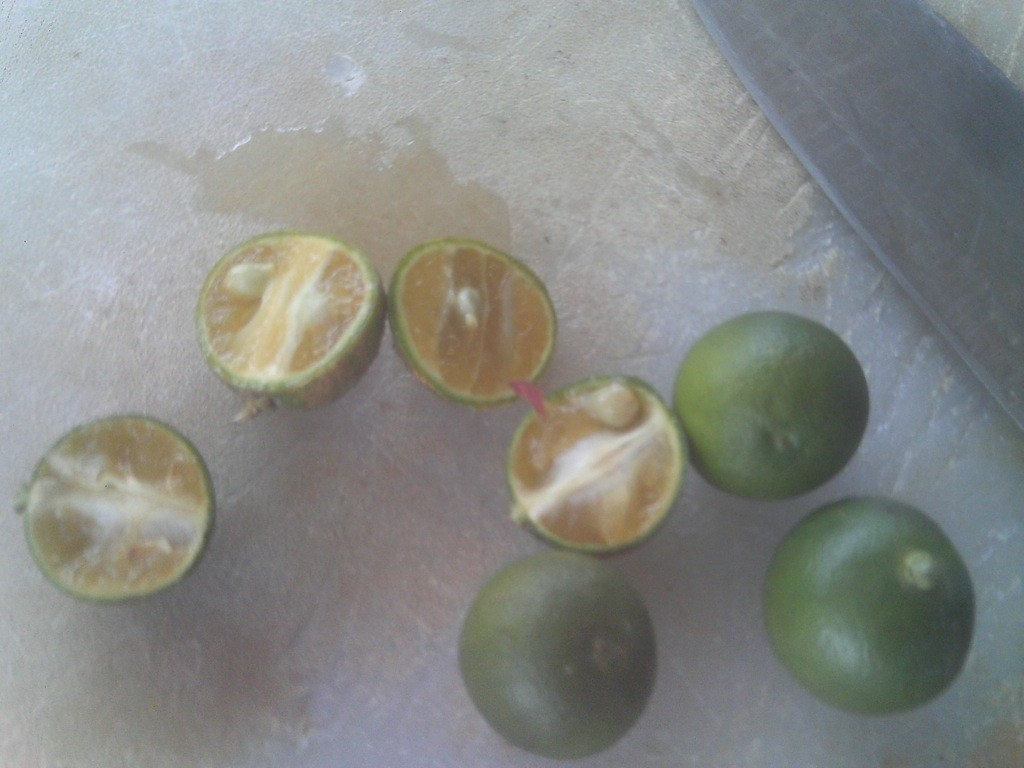 Cut and uncut calamansi fruit on chopping board