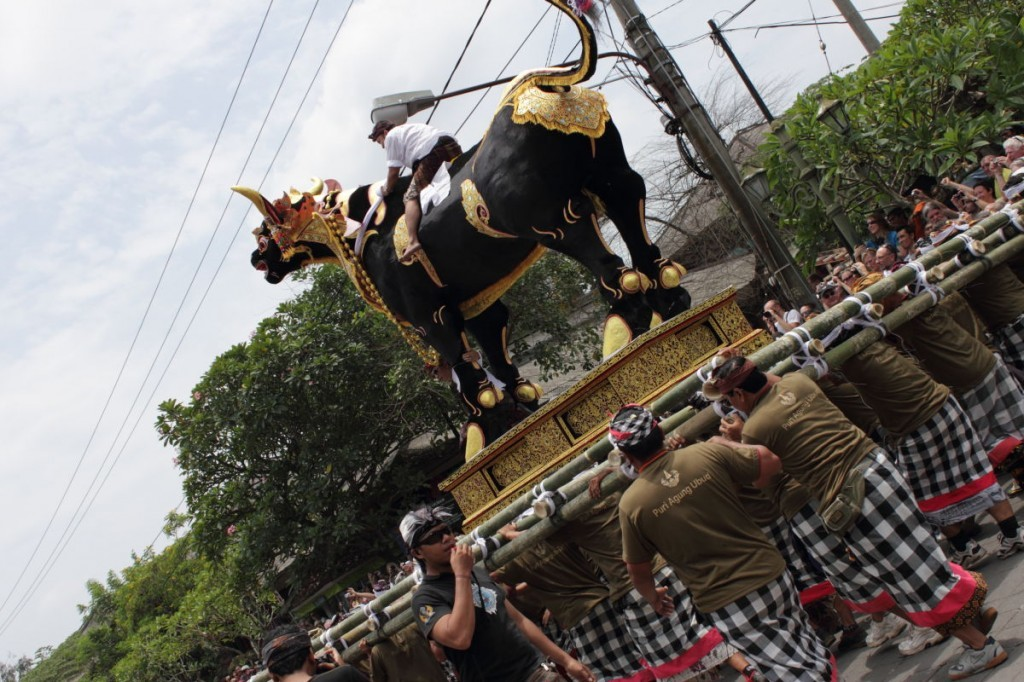 Bali cremation: men from the banjar carry a bull sarcophagus, with rider and MC.