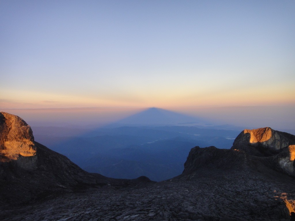 The shadow of Low's Peak refracts the sunrise: Mount Kinabalu, Borneo, Malaysia.