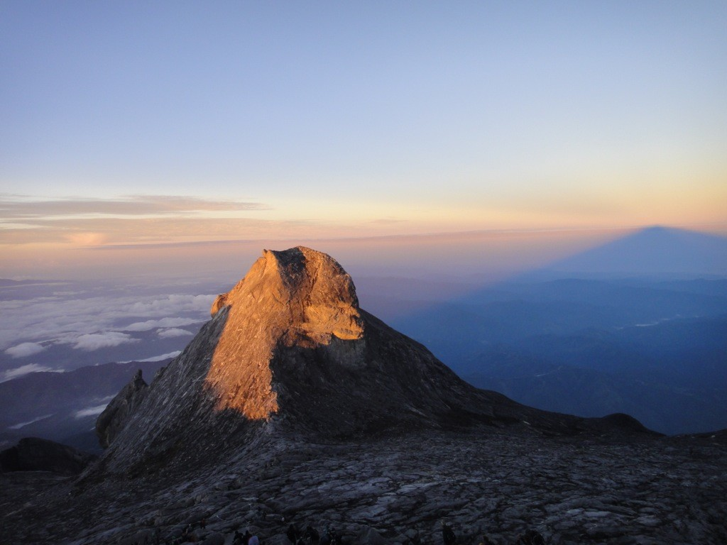 Low's Peak casts a shadow and refracts the sunrise, Mount Kinabalu, Borneo, Malaysia.