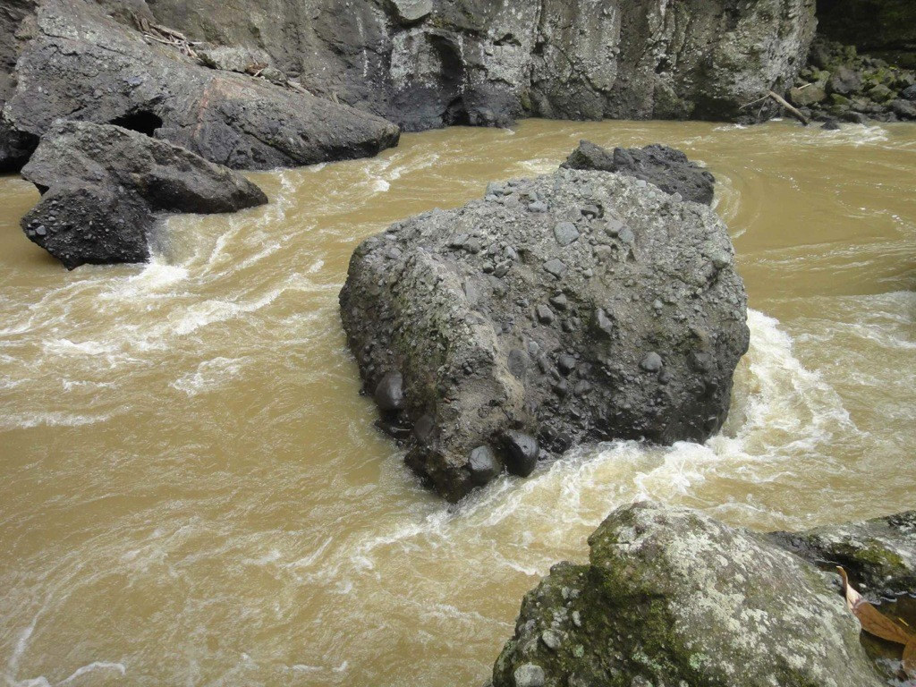 Maiting River swirls around dark rocks in gorge. Tana Toraja, Sulawesi, Indonesia.