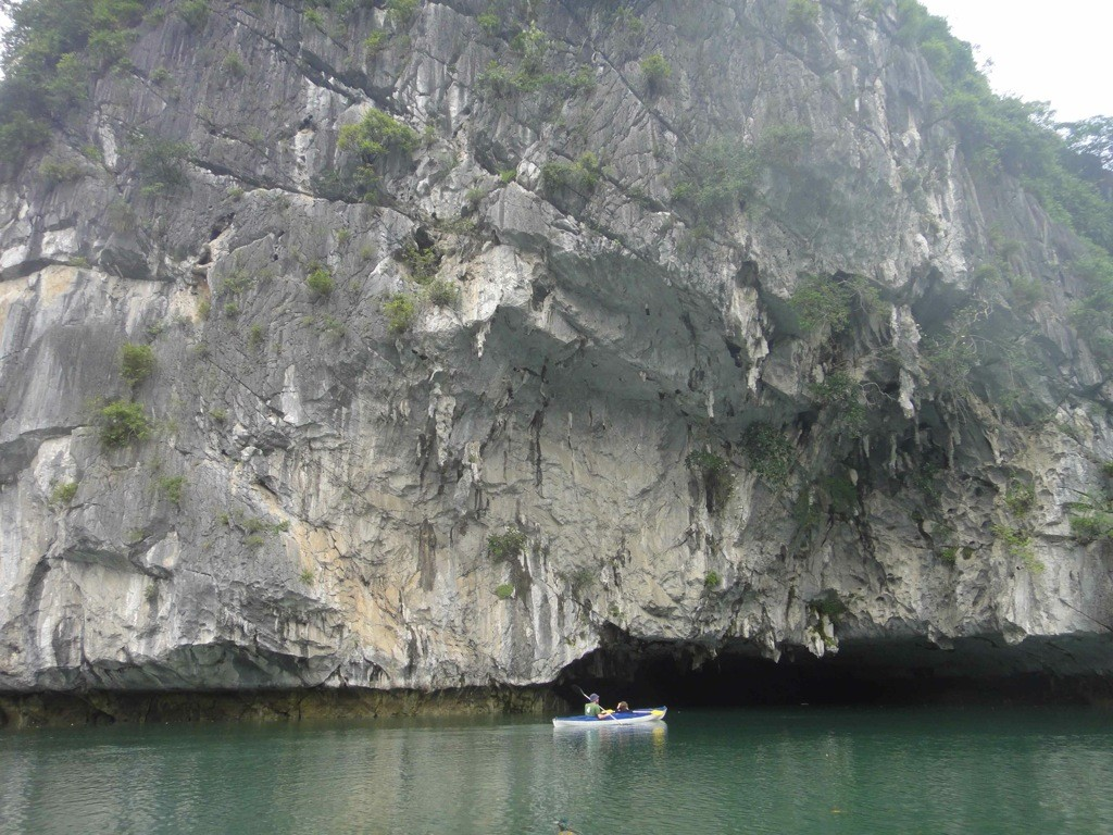 Kayak approaching gap in base of limestone cliff: Halong Bay, Vietnam.