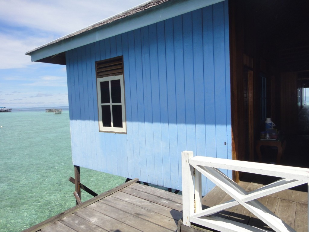 Room on stilt pier over jade green sea. Losmen Danakan, Pulau Derawan, Indonesia.