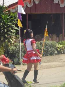 Girl in short skirt and knee boots leading political parade in Rantepao, Sulawesi, Indonesia.