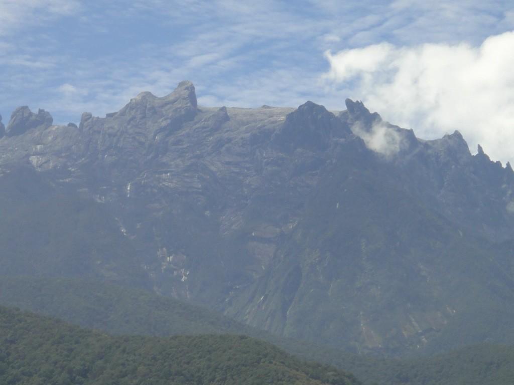 The spiky, lunar peaks of Mount Kinabulu framed by sky and tea plantations. Sabah, Borneo, Malaysia.