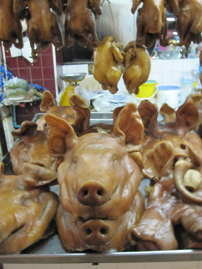 Pigs heads and other delicacies on sale in Trat market, Thailand