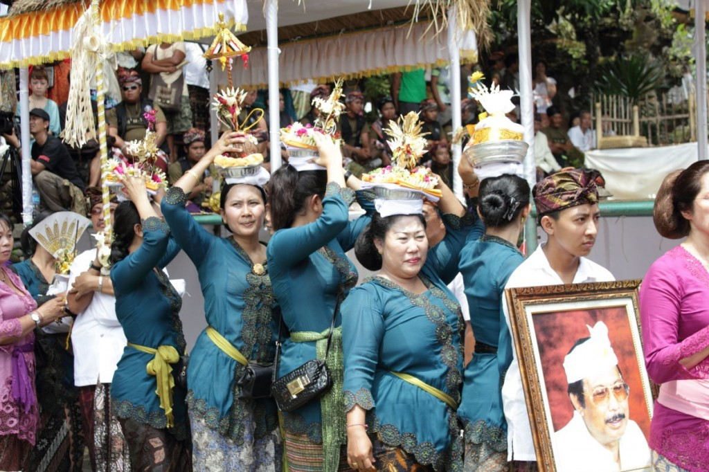 Bali cremation: women in blue blouses and gold sashes process with offerings on their heads and a portrait of the deceased.