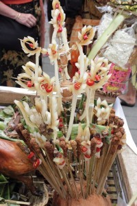 Bali cremation offerings including sticks of sate lilit and elaborate coloured rice dough figures in yellow and pink