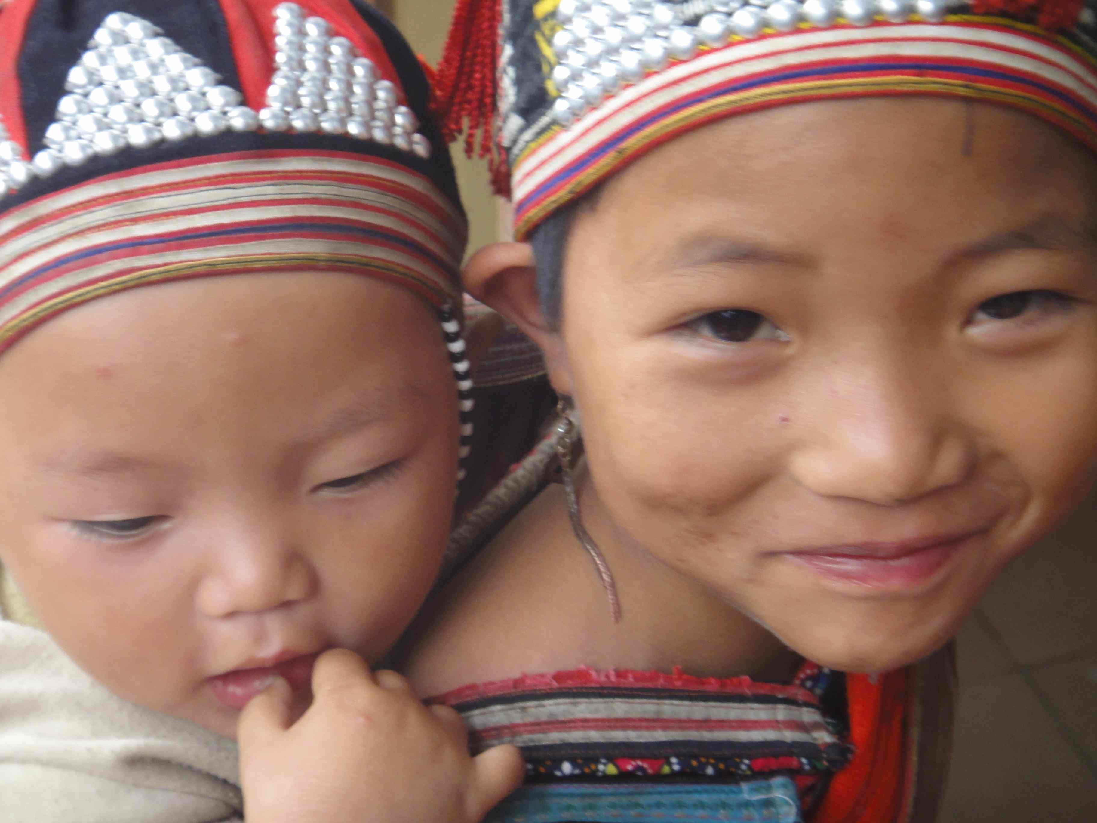 Hmong girl with her brother on back, smiling for the camera, Sapa, Vietnam.