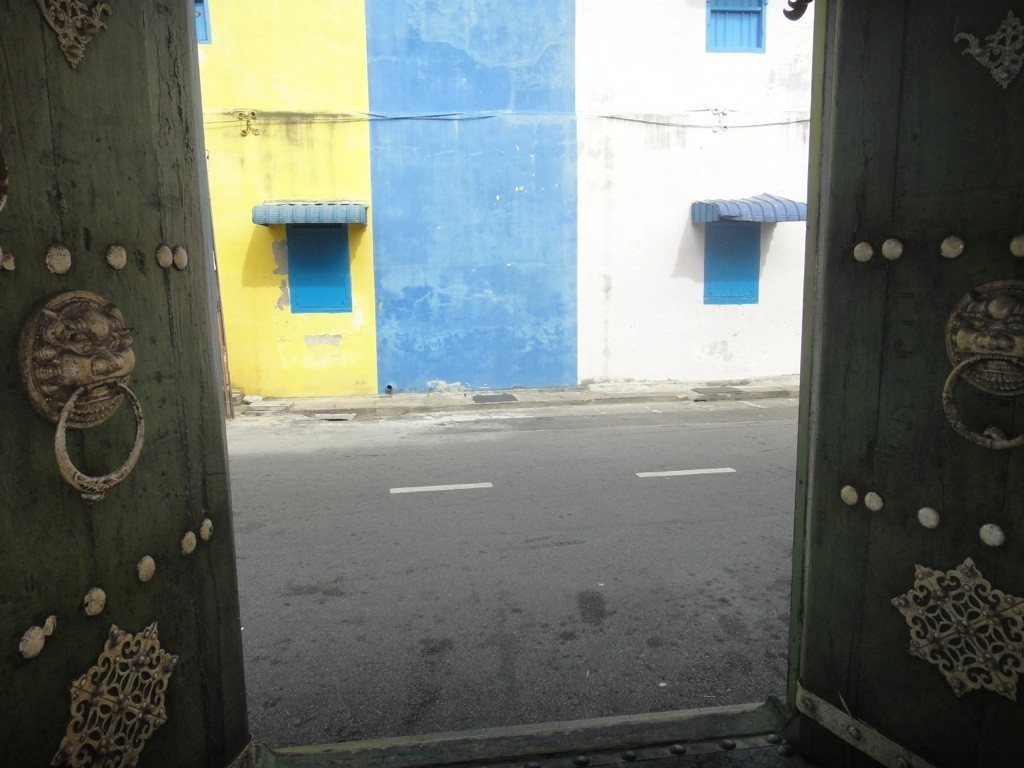 coloured shophouse fronts between ornate doors in georgetown, penang, malaysia.