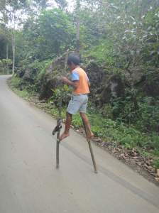 Torajan boy racing along the street on bamboo stilts. Tana Toraja, Sulawesi, Indonesia.