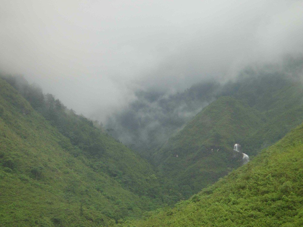 clouds descend over mountain gorge with waterfall visible in distance. Sapa, Vietnam.