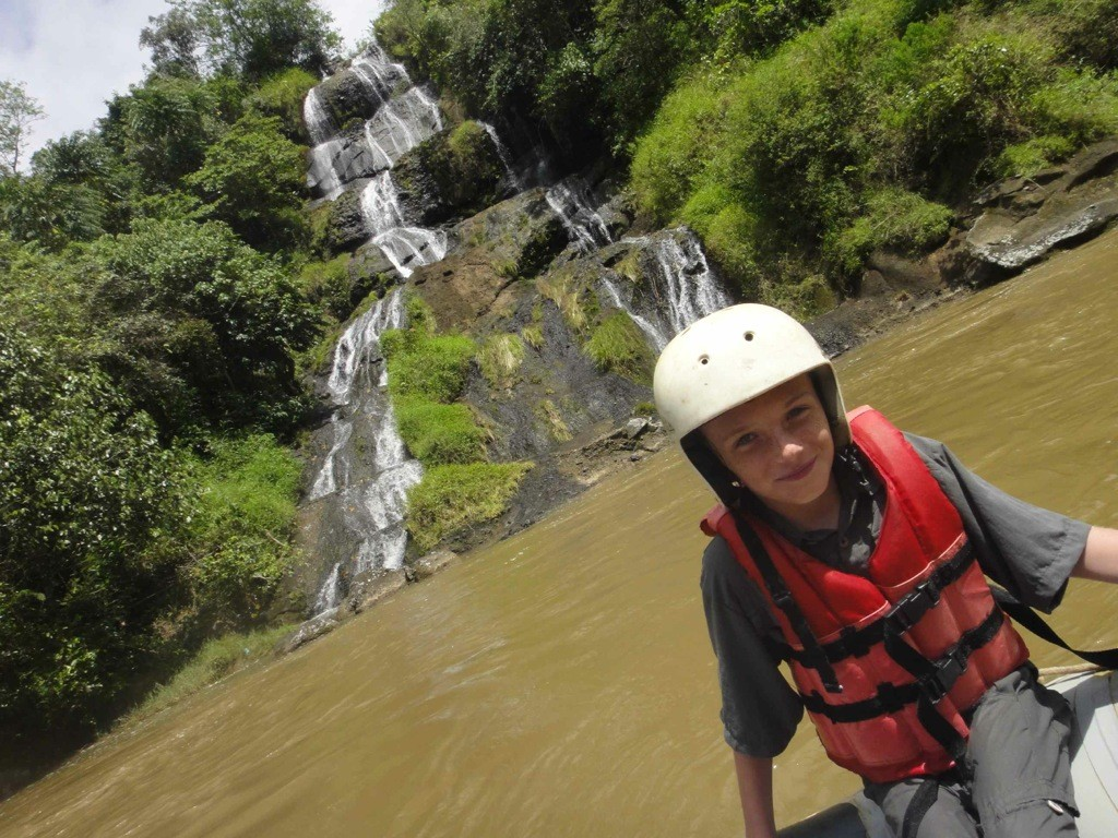 Z sits on edge of raft, in front of tumbling waterfall, Maiting River, Tana Toraja, Sulawesi, Indonesia.