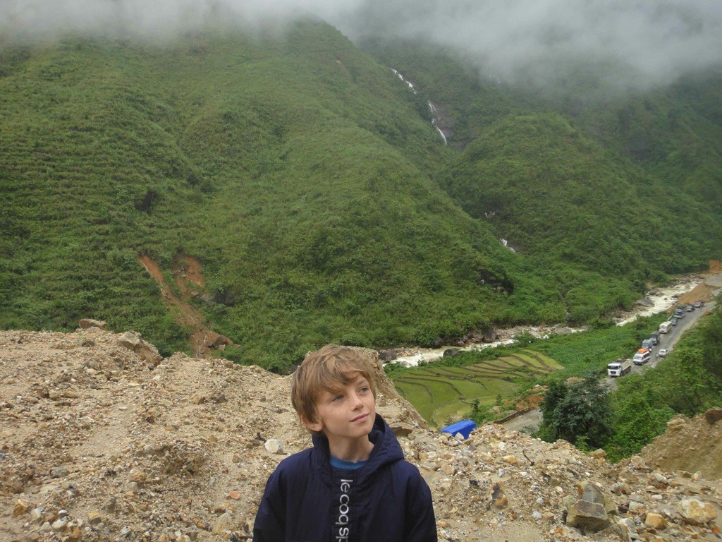 Zac at a gorge near Sapa, Vietnam, with building trucks in the background.