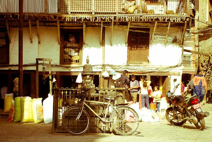 Bicycles, motorbikes and grain vendors in a medieval tenement, Kathmandu.