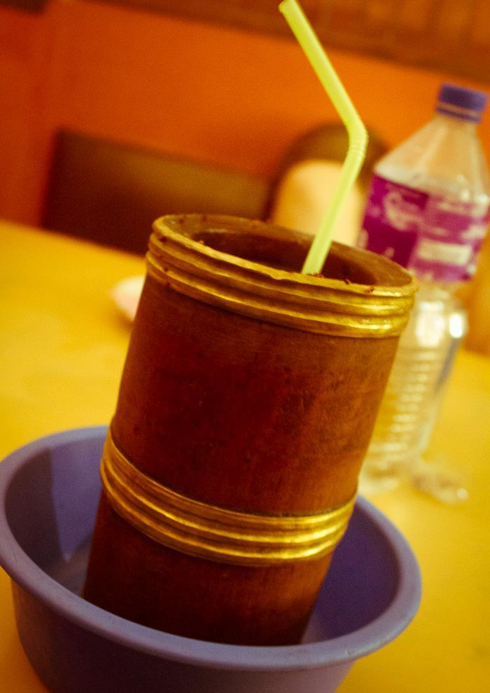 Tibetan millet beer -- tongba -- served in gilded bamboo stem.