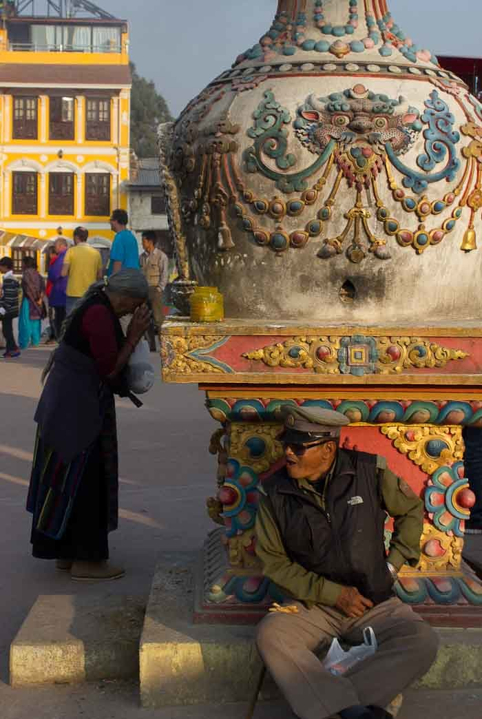 Policeman and old lady praying, Bodhnath stupa, Nepal.